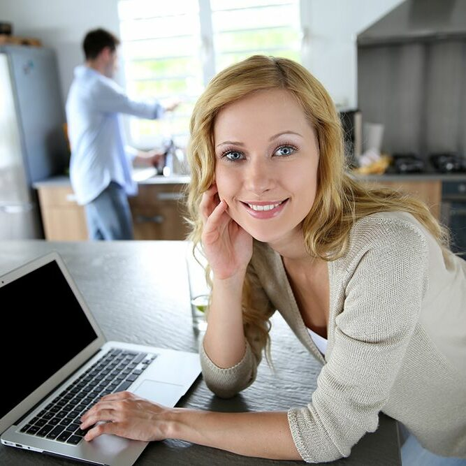 Cheerful blond girl connected on internet in home kitchen